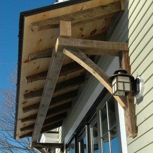 Cette photo montre une façade de maison beige tendance de taille moyenne et à un étage avec un revêtement en panneau de béton fibré et un toit à deux pans.