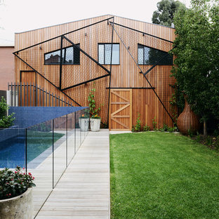 Design ideas for a contemporary two-storey brown exterior in Melbourne with wood siding and a gable roof.