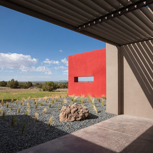 Large contemporary gray one-story adobe flat roof idea in Albuquerque