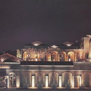 Inspiration för ett mellanstort medelhavsstil beige hus, med två våningar, stuckatur, valmat tak och tak med takplattor