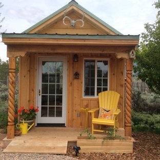 Imagen de fachada marrón, de estilo americano, pequeña, de una planta, con revestimiento de madera y tejado a dos aguas
