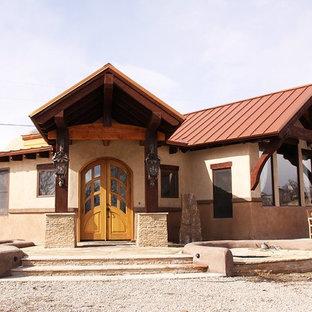 Ejemplo de fachada beige, rural, grande, de una planta, con revestimiento de adobe y tejado a dos aguas