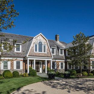 Ejemplo de fachada de casa multicolor, tradicional, grande, de dos plantas, con tejado a doble faldón y tejado de teja de madera