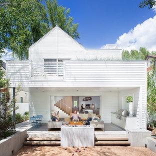 Immagine della facciata di una casa unifamiliare bianca scandinava a due piani con tetto a capanna