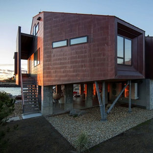 Inspiration for a beach style brown two-story metal house exterior remodel in Boston with a metal roof and a shed roof