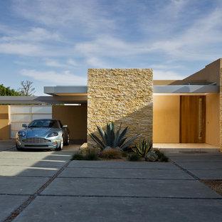 Diseño de fachada amarilla, moderna, grande, de una planta, con revestimientos combinados y tejado plano