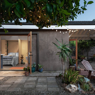 Small beach style gray one-story stucco exterior home photo in Los Angeles with a shingle roof