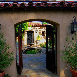 Foto de fachada de casa beige, mediterránea, de tamaño medio, de una planta, con revestimiento de estuco, tejado a dos aguas y tejado de teja de barro
