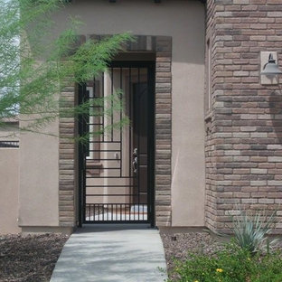 Large southwest brown two-story stone exterior home photo in Phoenix