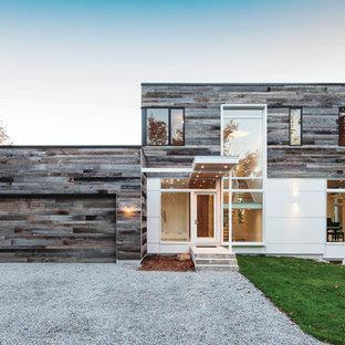 Diseño de fachada blanca, moderna, grande, de dos plantas, con revestimiento de madera y tejado plano