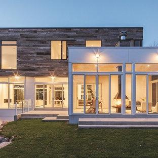 Foto de fachada blanca, minimalista, grande, de tres plantas, con revestimiento de madera y tejado plano