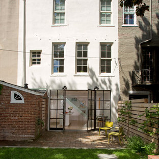 Large transitional white three-story stucco flat roof idea in DC Metro