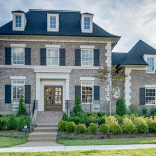 Large and gey traditional brick exterior in Nashville with three or more floors and a hip roof.