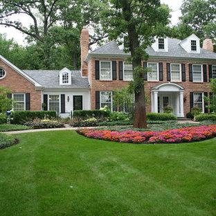 Imagen de fachada roja, clásica, grande, de dos plantas, con revestimiento de ladrillo y tejado a cuatro aguas