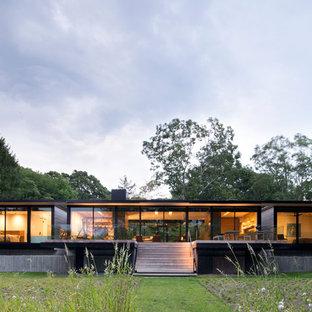 Foto della facciata di una casa unifamiliare moderna a un piano di medie dimensioni con tetto piano e rivestimento in vetro