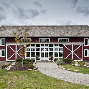 Foto della facciata di una casa grande in campagna a tre o più piani con rivestimento in legno