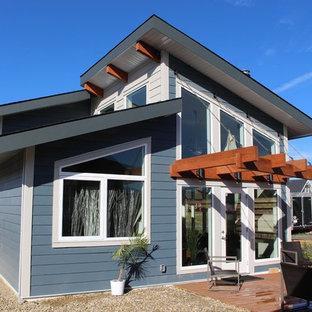 カルガリーの小さいビーチスタイルのおしゃれな家の外観 (コンクリート繊維板サイディング、青い外壁) の写真