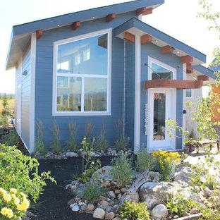 Modelo de fachada de casa azul, costera, pequeña, de una planta, con revestimiento de aglomerado de cemento y tejado a dos aguas