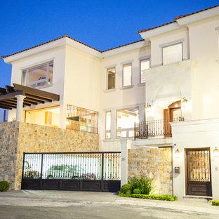 Ejemplo de fachada de casa amarilla, mediterránea, grande, de tres plantas, con revestimiento de hormigón y tejado de teja de barro