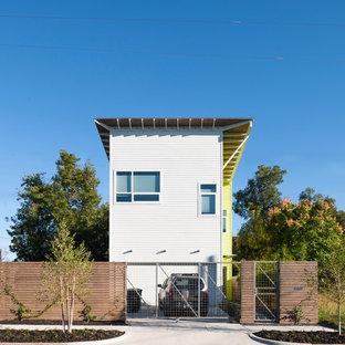 Foto della facciata di una casa bianca contemporanea a due piani con rivestimento con lastre in cemento
