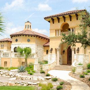 Foto de fachada amarilla, mediterránea, extra grande, de dos plantas, con tejado a cuatro aguas y revestimientos combinados