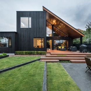 Immagine della facciata di una casa unifamiliare nera contemporanea a due piani con rivestimento in legno e tetto a una falda