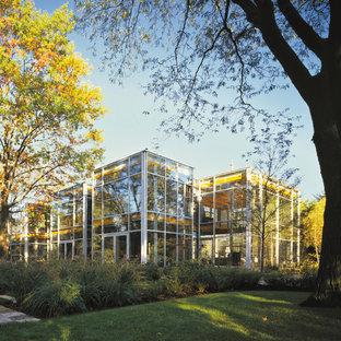 Новый формат декора квартиры: большой, двухэтажный фасад дома в современном стиле с облицовкой из стекла и плоской крышей