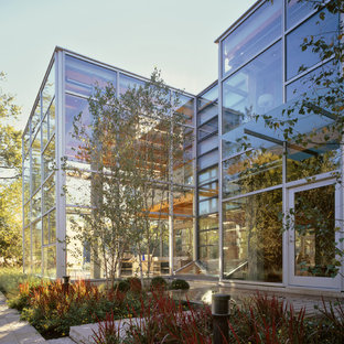 Example of a trendy two-story glass flat roof design in Chicago