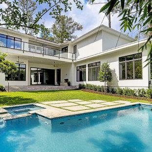 Cette photo montre une grand façade de maison blanche tendance à un étage avec un revêtement en stuc et un toit en shingle.