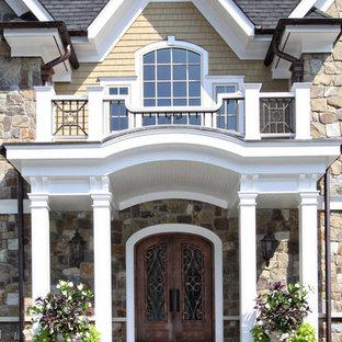 Diseño de fachada de casa amarilla, clásica, grande, de dos plantas, con revestimientos combinados, tejado a cuatro aguas y tejado de teja de madera