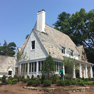 Inspiration for a large timeless white three-story stucco exterior home remodel in New York with a mixed material roof