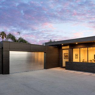 Exempel på ett modernt svart hus, med allt i ett plan, metallfasad och platt tak