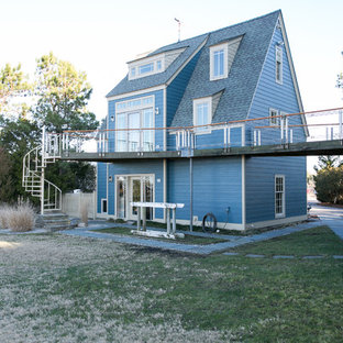 Modelo de fachada azul, moderna, grande, de tres plantas, con revestimiento de madera y tejado a dos aguas