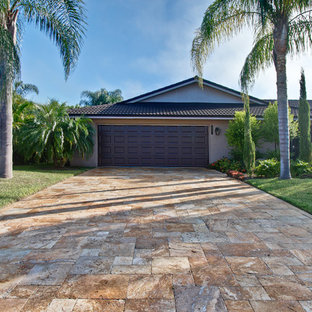 Inspiration for a mid-sized rustic beige one-story stone exterior home remodel in Tampa