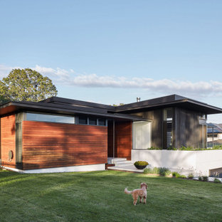 Contemporary brown house exterior in Brisbane with wood siding and a shed roof.