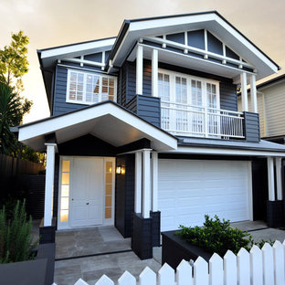 This is an example of a traditional two-storey black house exterior in Brisbane with wood siding and a gable roof.
