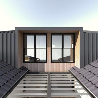 Foto della facciata di un appartamento piccolo grigio contemporaneo a tre o più piani con rivestimento in metallo, tetto a padiglione e copertura mista
