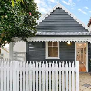 Inspiration for a beach style one-storey black house exterior in Sydney with a gable roof.