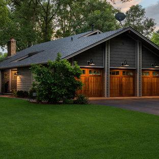 Modelo de fachada de casa gris, de estilo americano, de tamaño medio, a niveles, con revestimiento de madera, tejado a dos aguas y tejado de teja de madera