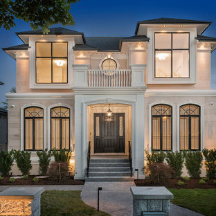 Example of a large french country white two-story stone house exterior design in Vancouver with a hip roof and a shingle roof
