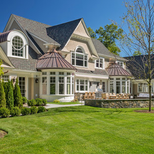 Design ideas for a traditional two-storey beige exterior in Boston with wood siding and a gable roof.