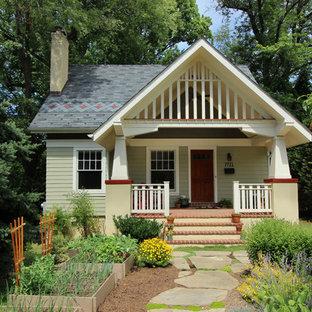 Modelo de fachada verde, de estilo americano, pequeña, de dos plantas, con revestimiento de madera y tejado a dos aguas