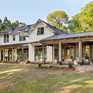 Idéer för lantliga beige hus, med två våningar, sadeltak och tak i metall