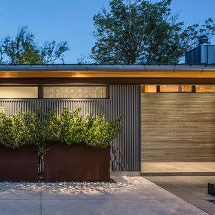 Ejemplo de fachada de casa azul, contemporánea, de tamaño medio, de dos plantas, con revestimiento de metal, tejado plano y tejado de metal