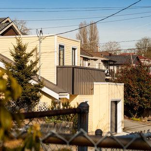 Modelo de fachada amarilla, contemporánea, pequeña, de dos plantas, con tejado plano y techo verde