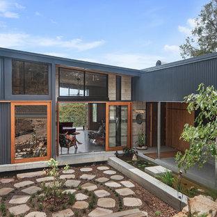 Imagen de fachada de casa multicolor, minimalista, grande, de dos plantas, con revestimiento de metal, tejado plano y tejado de metal