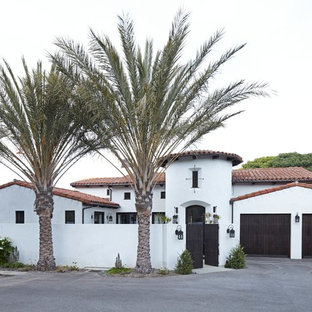 Mid-sized tuscan white one-story stucco exterior home photo in Los Angeles with a tile roof