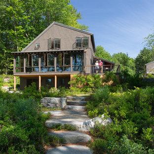 Modelo de fachada de casa marrón, clásica renovada, de tamaño medio, de dos plantas, con revestimiento de madera, tejado a dos aguas y tejado de metal