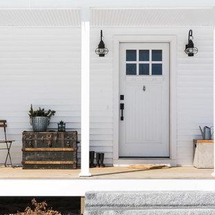 Foto de fachada de casa blanca, de estilo de casa de campo, de tamaño medio, de dos plantas, con revestimiento de vinilo, tejado a dos aguas y tejado de teja de madera
