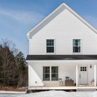 Example of a mid-sized farmhouse white two-story vinyl exterior home design in Portland Maine with a shingle roof